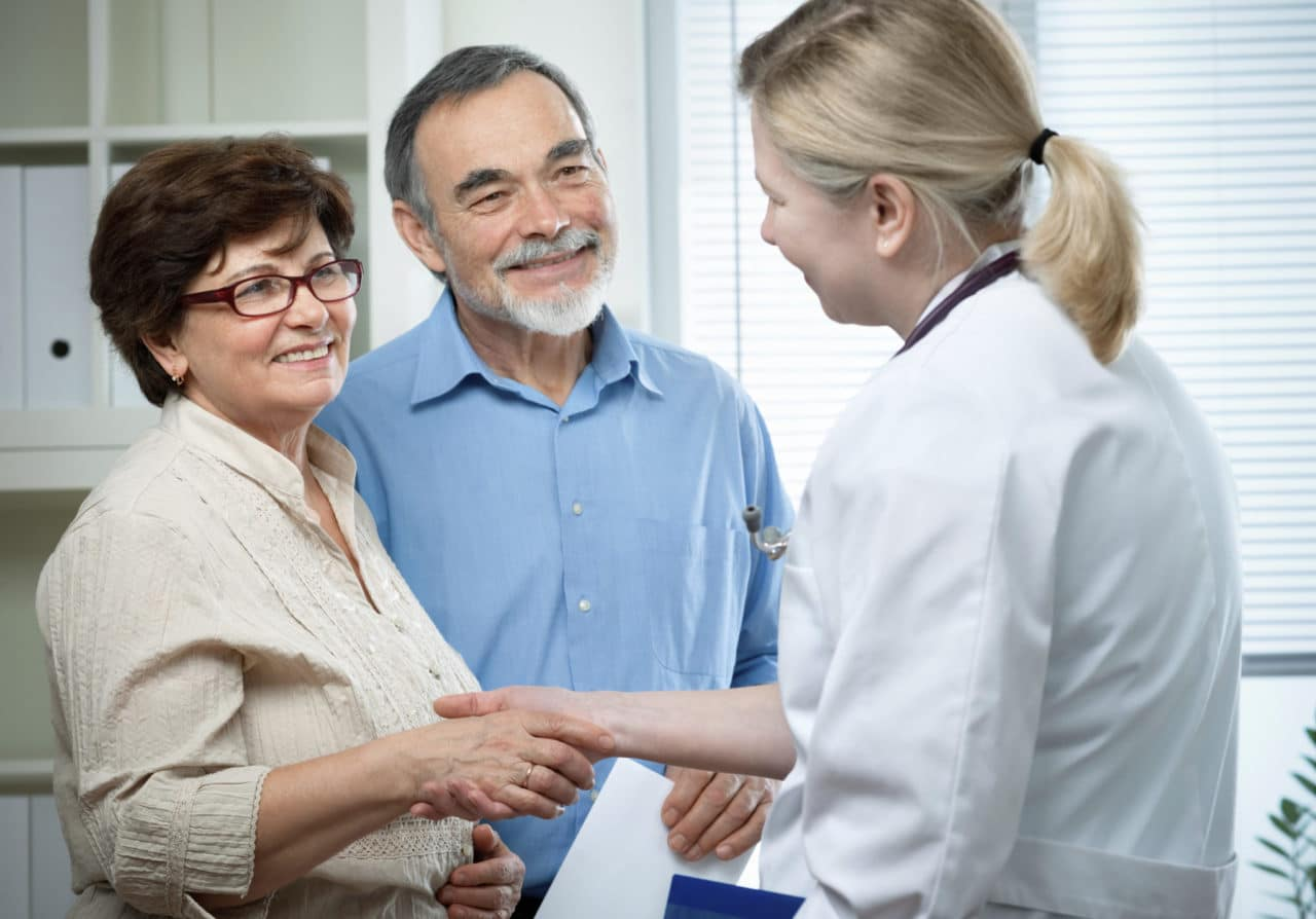 Photo of an older couple meeting an audiologist.
