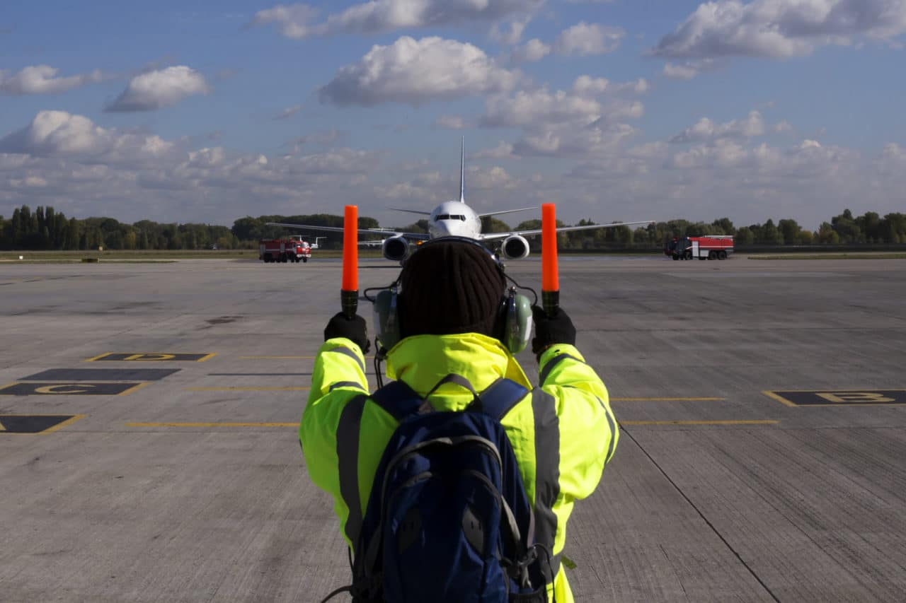 Photo of a person directing an airplane with reflective gear and ear protection
