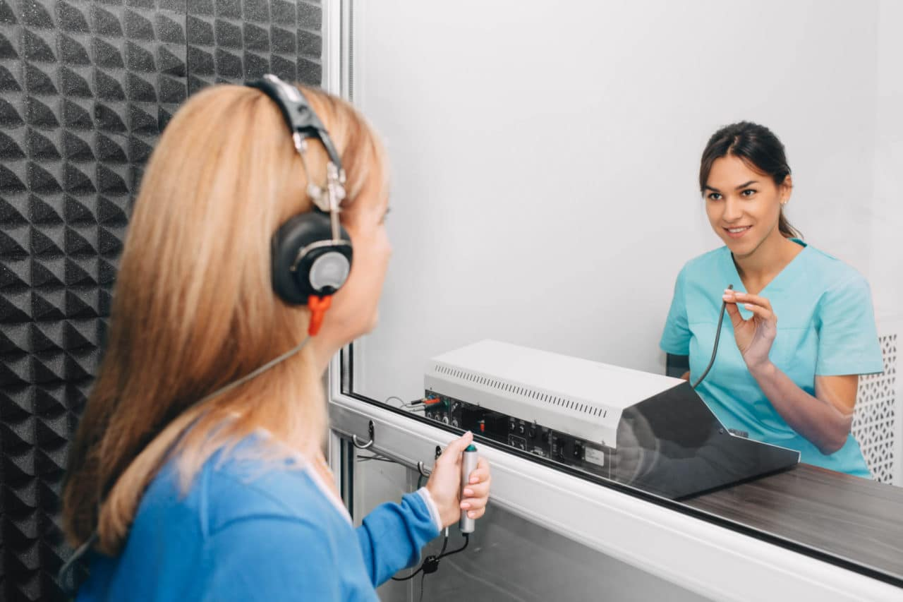 Photo of a person wearing earphones and facing a technician administering a hearing test through a window.