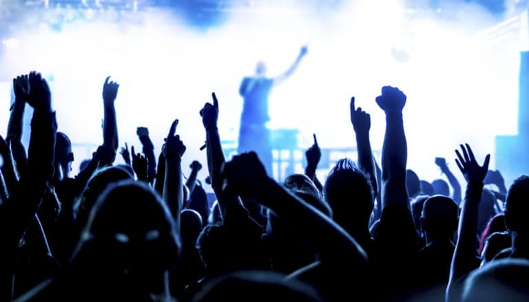 Photo of a crowd raising their hands at a concert with the blown-out performer onstage in the background.