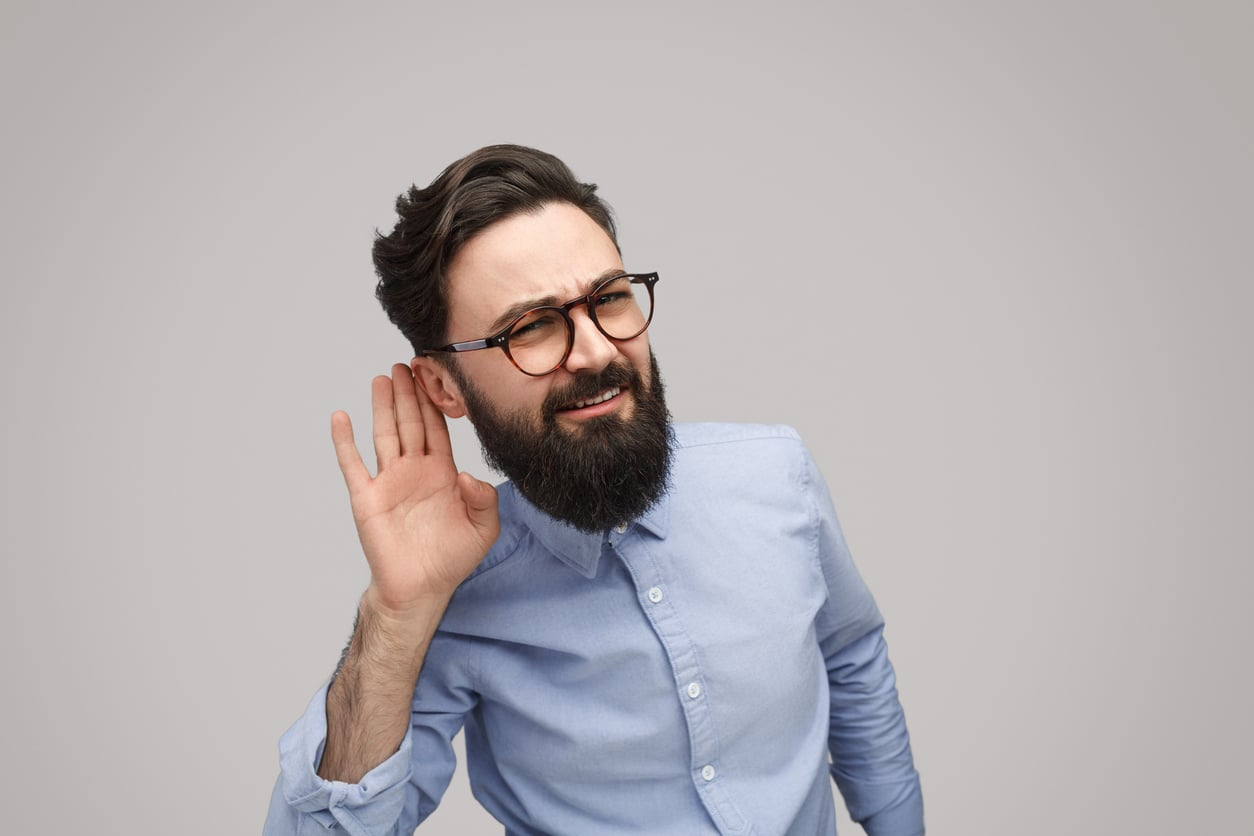 Younger man putting his hand to his ear in a listening fashion