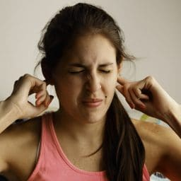 Young woman disturbed by loud noise pollution