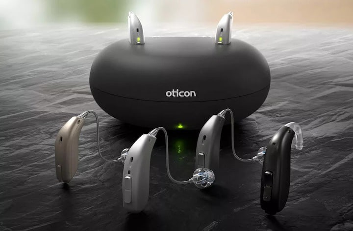 Oticon hearing aids with a charging base behind them