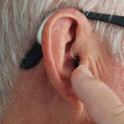 Man points at his hearing aid